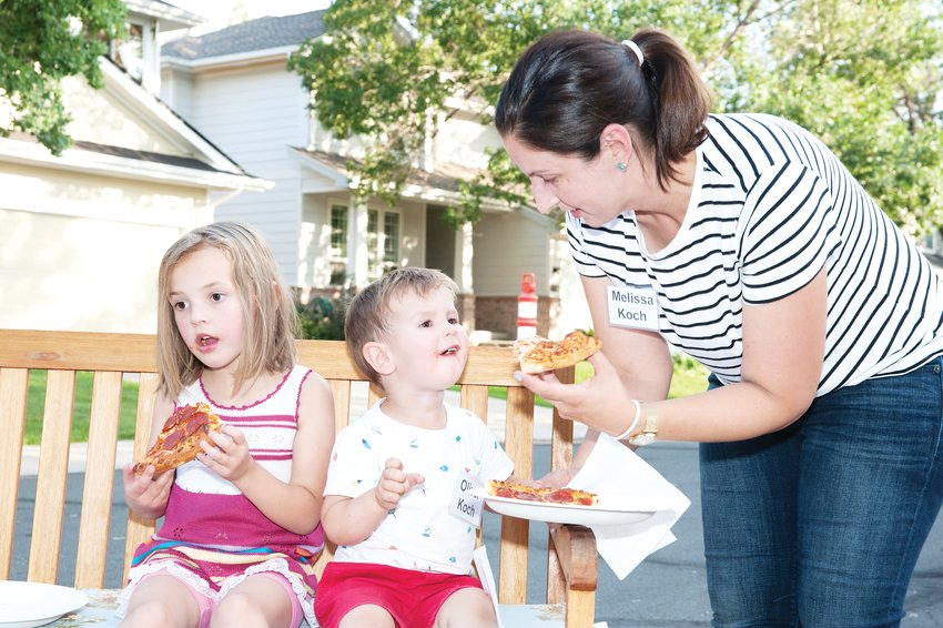 Melissa Koch, right, of Thornton, feeds her son Oliver, 2, and Anna, 4 some pizza, during a National Night Out party at the Greens at Hunter's Glen August 6.