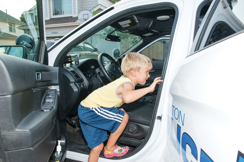 Caleb Boerner, 5, of Thornton, climbs into a Thornton Police Department cruiser, during a National Night Out party on Thornton's Humboldt Way August 6.