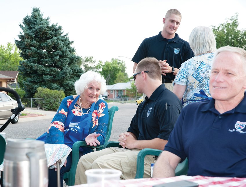 Ruth Duncan, left, visits with Northglenn Police Cadet Patrick Day, during a National Night Out stop at Duncan's home on August 6. Duncan and neighbor Bridget Mathews hosted a chili cookout at the intersection of Logan Court and Northglenn Drive on the city's east side.
