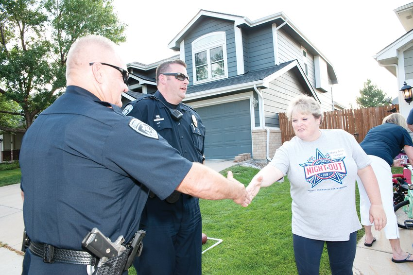 Mary Ann Yeager, right, of Thornton, greets Thornton P.D. Officers Mark Quintana, left, and Levi Husk, during a National Night Out stop at the home of Becky Harper in Hunter's Glen August 6.