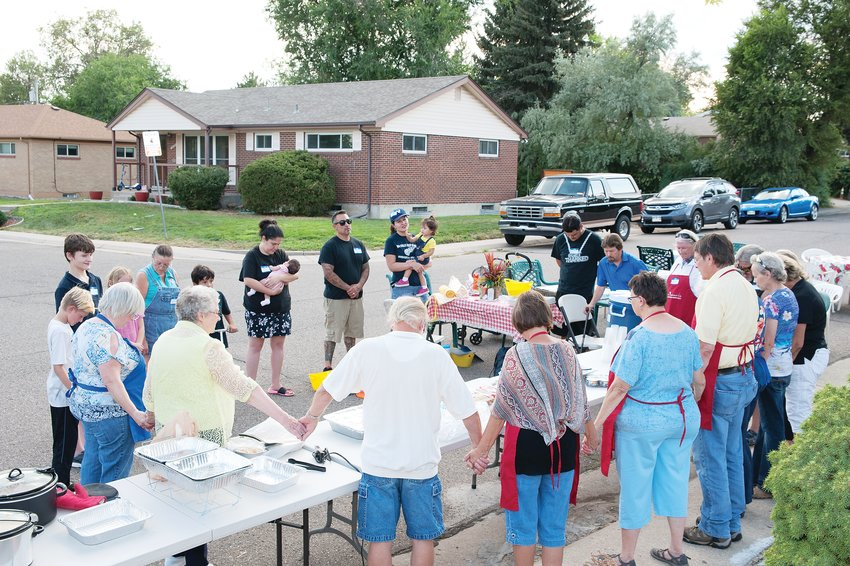 Neighborhood residents at Northglenn Drive and Logan Court pause for a group prayer, prior to their meal during National Night Out August 6.