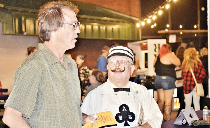 David Nielsen of Centennial, left, and Roger Hadix chat just outside the bar at Northglenn's Magic Fest Aug. 17. Hadix, of Colorado Springs, said he wore his historic baseball costume to the festival, in keeping with the event's masquerade theme.
