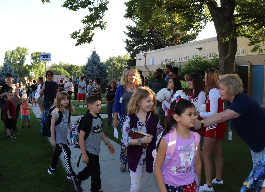 Students high-five Thomson staff members and Arvada High School cheerleaders on their way into Thomson for the first time in the 2019-2020 school year.