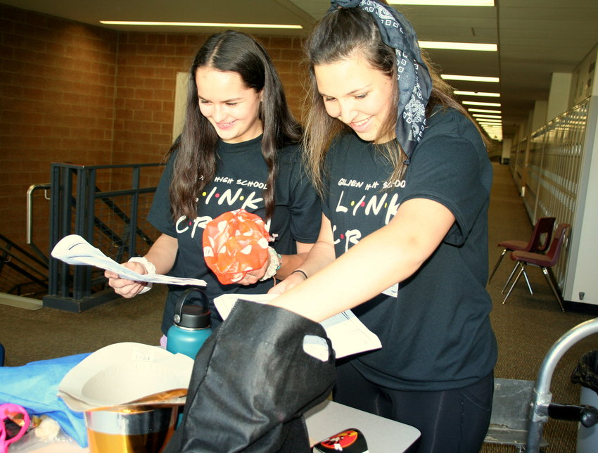 Veronica Rogers, left, and Gentry Keener, both juniors at Golden High School who are serving as LINK leaders this school year, look at schedules and pull out some of the supplies they brought for team-building activities on freshmen orientation day, which took place on Aug. 14.
