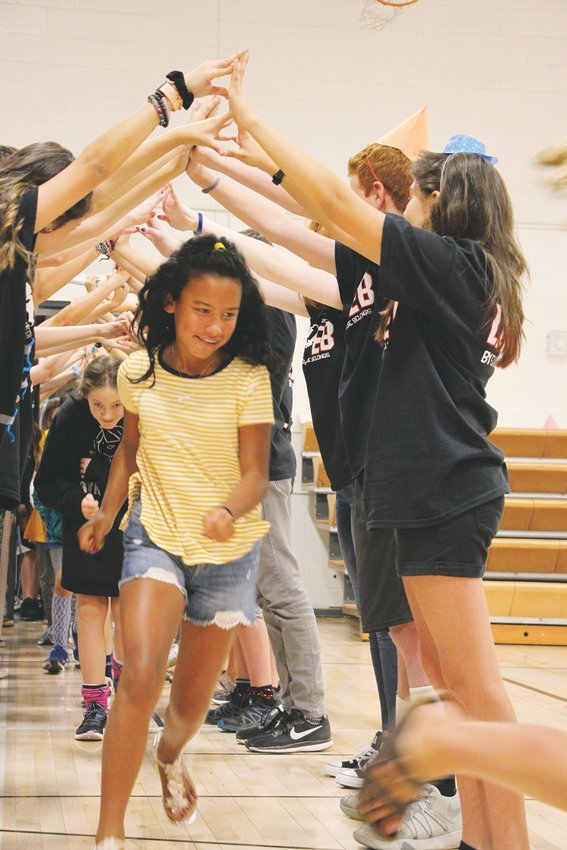 Incoming sixth graders run beneath the intertwined arms of student ambassadors from the upper grades, who welcomed them to their first day of middle school.