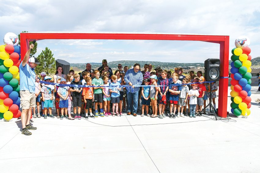 Mayor Jason Gray is joined by a group of children for the grand opening of the Deputy Zack S. Parrish III Memorial Park.