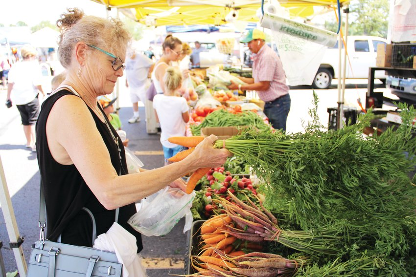 Elizabeth Latham, 70, examines produce at the Centennial Farmers Market Aug. 14. Dozens of customers strolled through around noon.