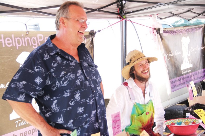 "Todd Smith, who goes by ""Tomato Todd,"" left, smiles with Colby Accacian while talking to a customer Aug. 14 at the Centennial Farmers Market. The weekly market assembles at 7424 S. University Blvd. in the former Albertsons parking lot."