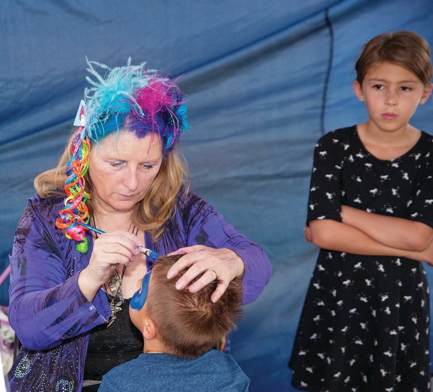 Face-painter Kelleen Raska puts the finishing touches on Kyden Lumaguip, 3, of Westminster, as his sister Rilynn, 8, looks on Aug. 17 at the third annual Northglenn Magic Fest, at the Northglenn Community Center.