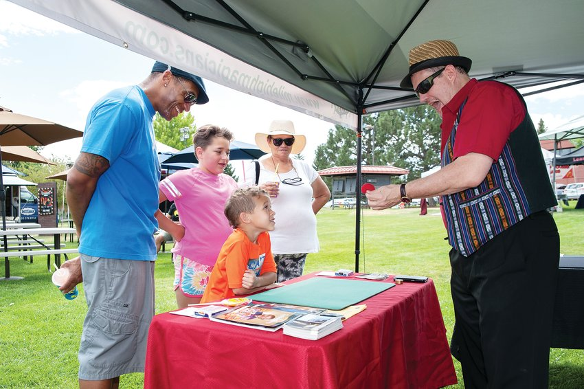 Jerome Hall III, second from left, of Henderson, helps magician Gene Gordon perfom a trick, as his father Jerome Hall, Jr., sister Zenaya, 11, and grandmother Bonnie look on, during Northglenn's annual Magic Fest August 17 at the Northglenn Community Center.