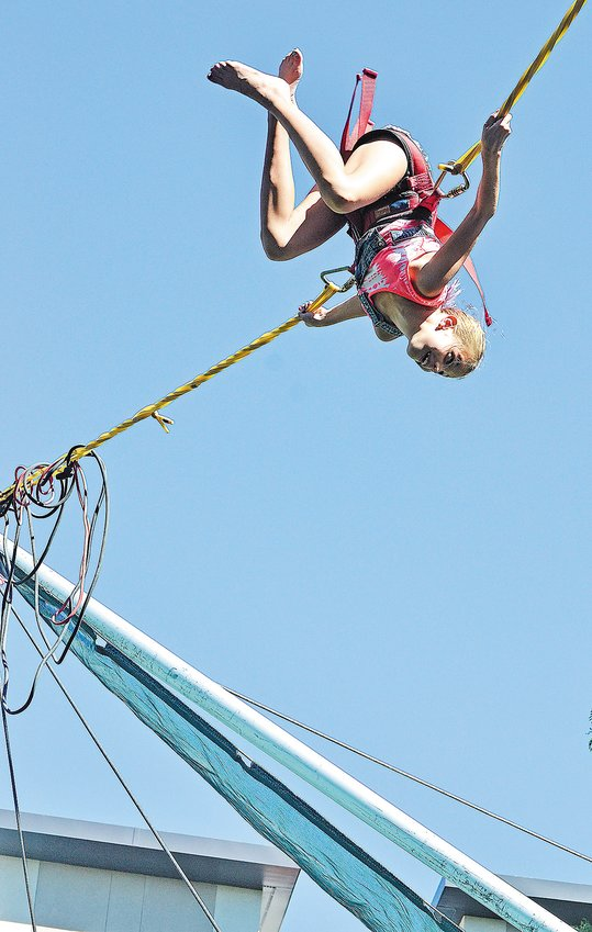 Aubrielle Wenzel, 9, of Arvada, does a flip while on a bungee ride at the Arvada Harvest Festival in 2016.