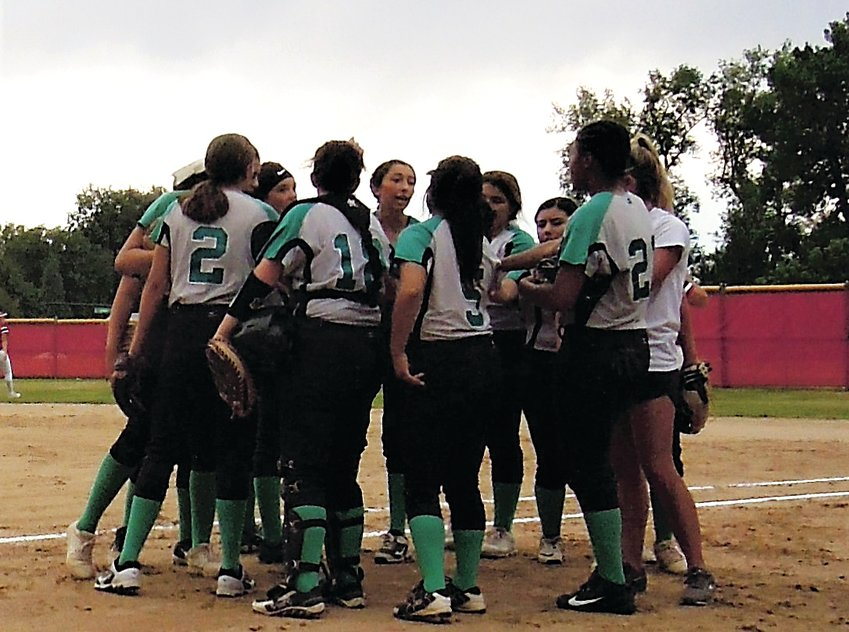 The Lady Wolves huddle after completing a half-inning against Denver East Aug. 23.