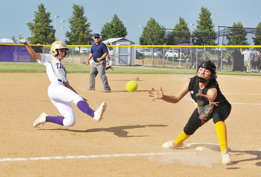 Holy Family baserunner Jenna Pfenning, left, attempts to reach third base safely as Wheat Ridge's Emeri Ortega takes the throw during an Aug. 20 game at Holy Family High School in Broomfield. The Tigers opened up defense of their CHSAA 4A State Title, with an 8-1 victory over the Lady Farmers.