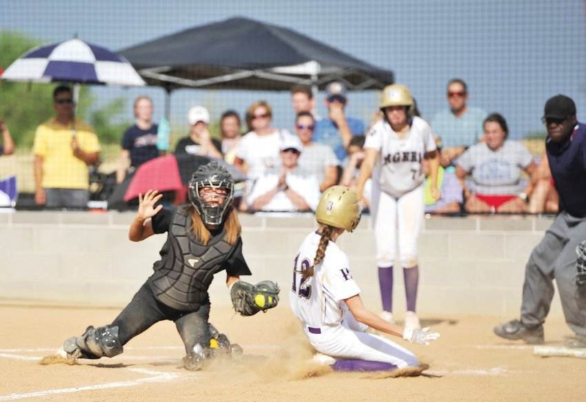 Wheat Ridge catcher Carly Storrer prepares to tag Holy Family's Ty Whitlock late in an Aug. 20 game at Holy Family High School in Broomfield. Though Whitlock was out, the Tigers' easily beat the Lady Farmers, 8-1.