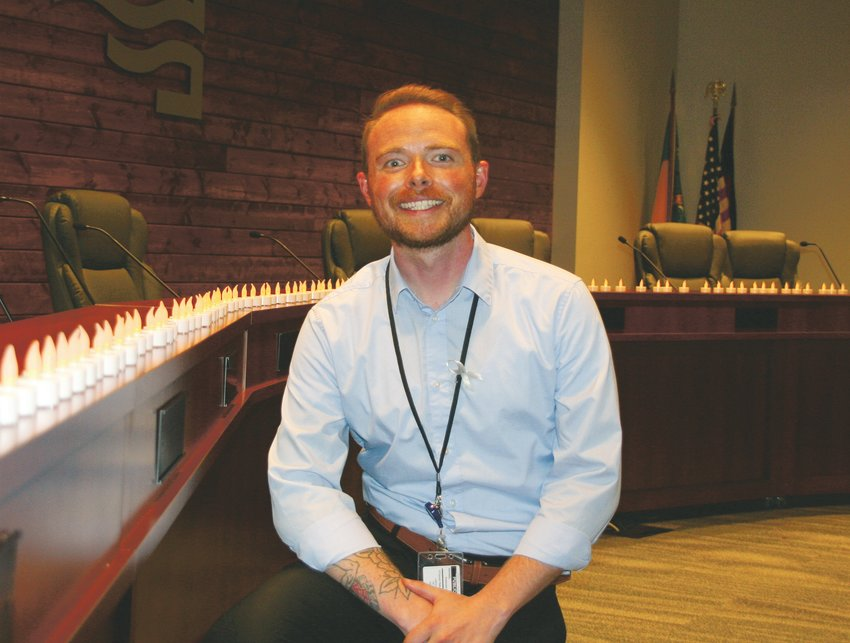 Michael Miller, the opioid initiatives coordinator with Jefferson County Public Health, kneels beside the candles set up in recognition of the 98 lives lost to drug overdose in Jefferson County in 2017. Jefferson County Public Health hosted its 2019 End Overdose Jeffco event on Aug. 27 at the Edgewater Civic Center.