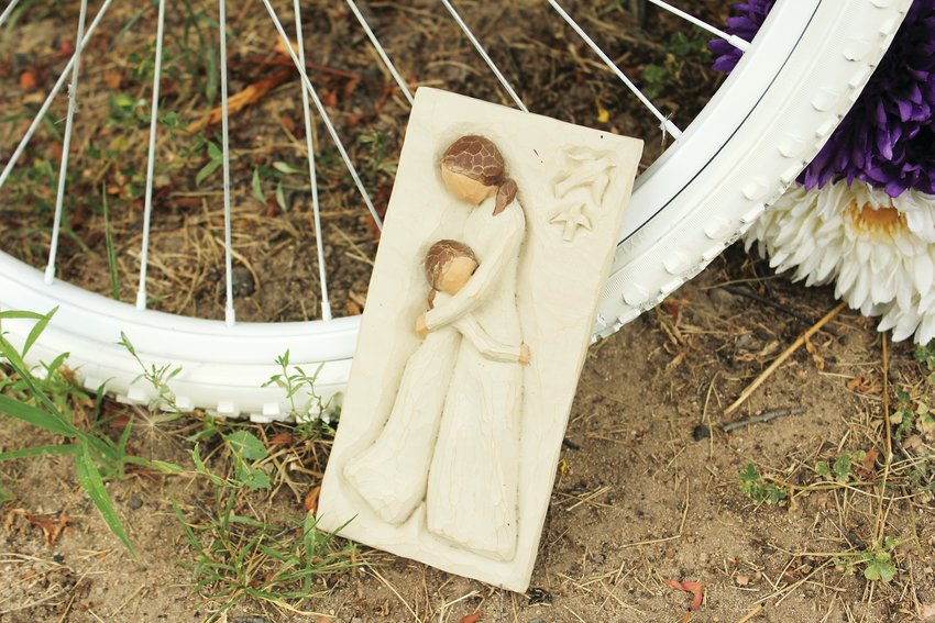 A plaque of a mother and child leans against Alexis Bounds' ghost bike in Denver. Bounds was the mother of two young boys.