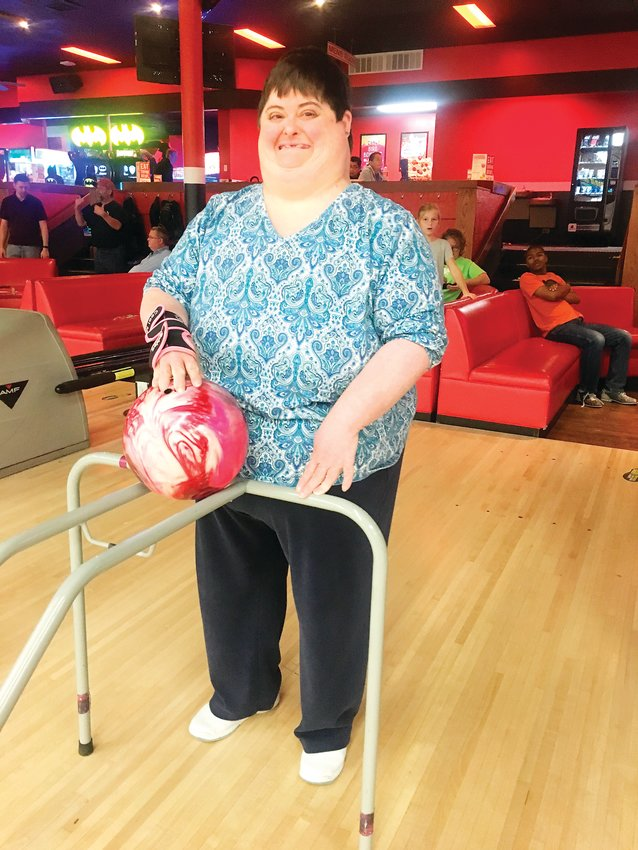 At a bowling outing with Denver Adaptive Recreation, a participant, Janna, prepares to bowl using adaptive equipment.