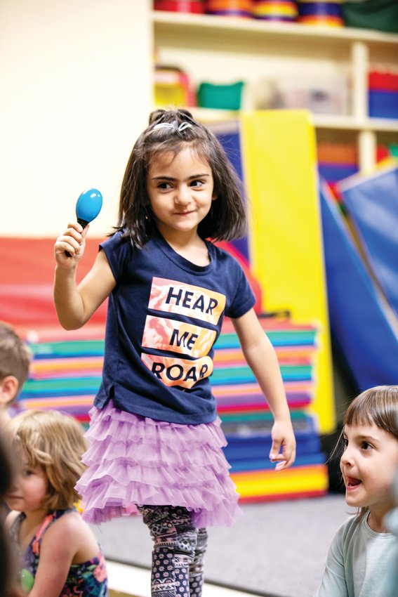 A student from Warren Village dances with a maraca during a music class with Swallow Hill. In addition to putting on concerts, Swallow Hill Music operates a school and does music outreach with programs such as Warren Village.