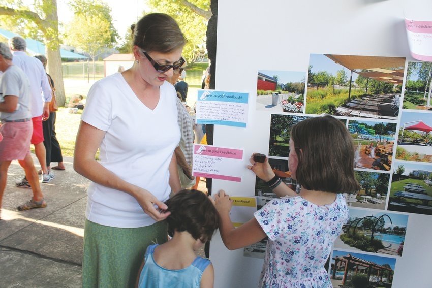 Rachel Griffin helps her daughters Emily and Kerry make comment cards for different amenities they are hoping for when the Congress Park pool is renovated. The city held a public meeting on the project in mid-August.