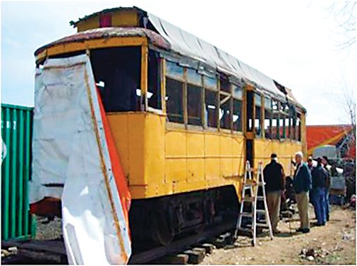 Members of the Friends of the .04 Trolley group prepare to load a streetcar onto the bed of a semi-truck. The group is restoring the trolley, which was one of the last to run in Denver.