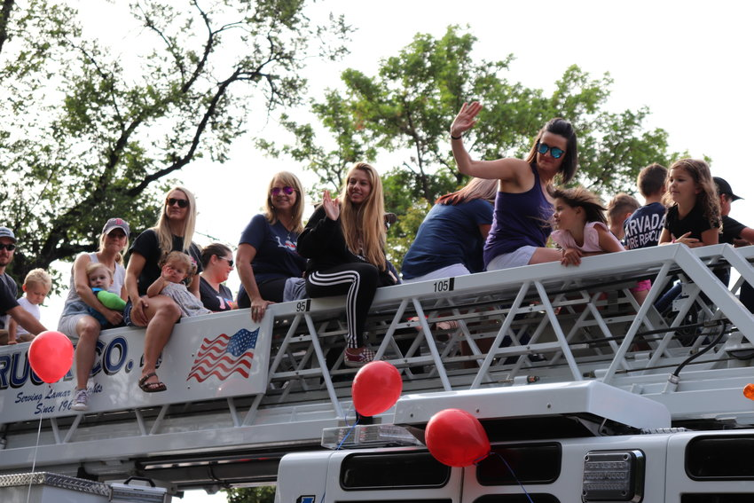 Locals ride on the top of an Arvada Fire truck during the parade.