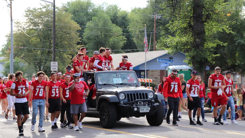 Football players show their support for Arvada High during the parade.