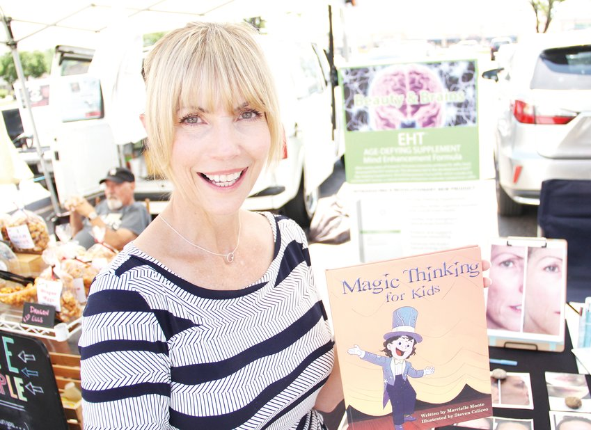 "Marrielle Monte Canales stands at the Centennial Farmers Market, holding a children's book she wrote called ""Magic Thinking for Kids,"" which teaches that they can change their feelings with positive self-talk."