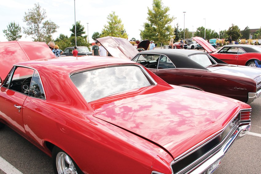 Cars with their hoods popped lined the rows of the parking lot at Centennial Center Park during the city's car show.