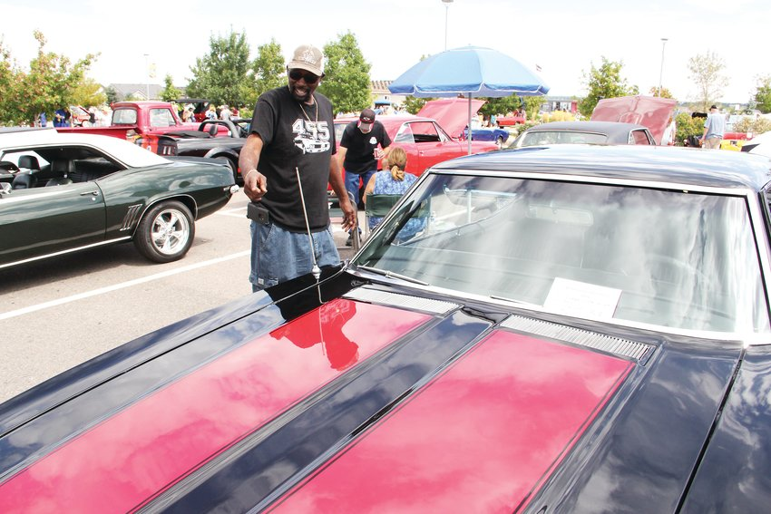 Dwayne Williams, 60, stands next to his 1969 Oldsmobile 442 W30 at the Centennial Car Show Sept. 7.