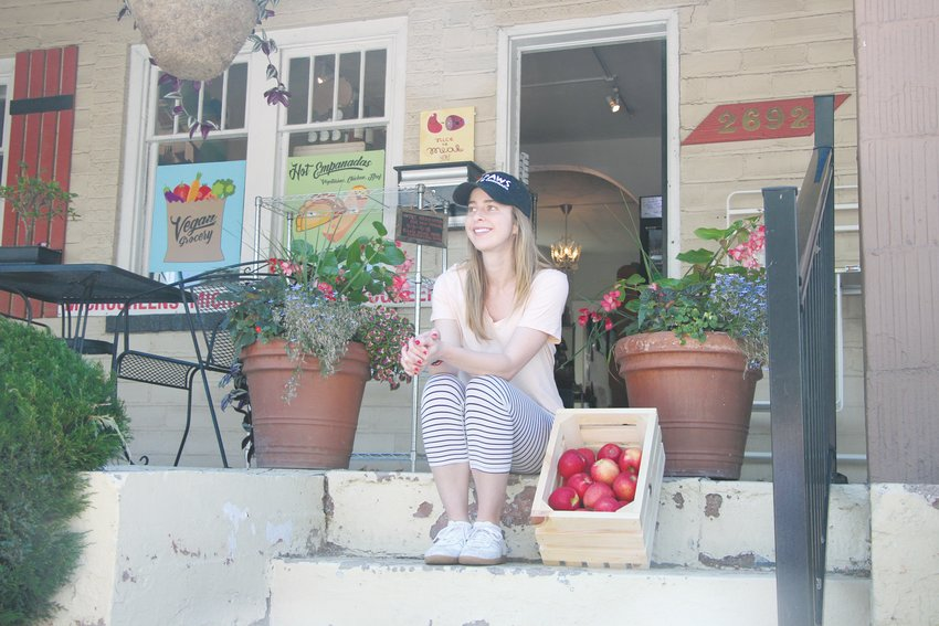 Hannah King, the owner of Littleton Market at 2692 West Alamo Ave, sits beside a crate of early-season apples. A cold spring means many summer crops are behind schedule, King said.