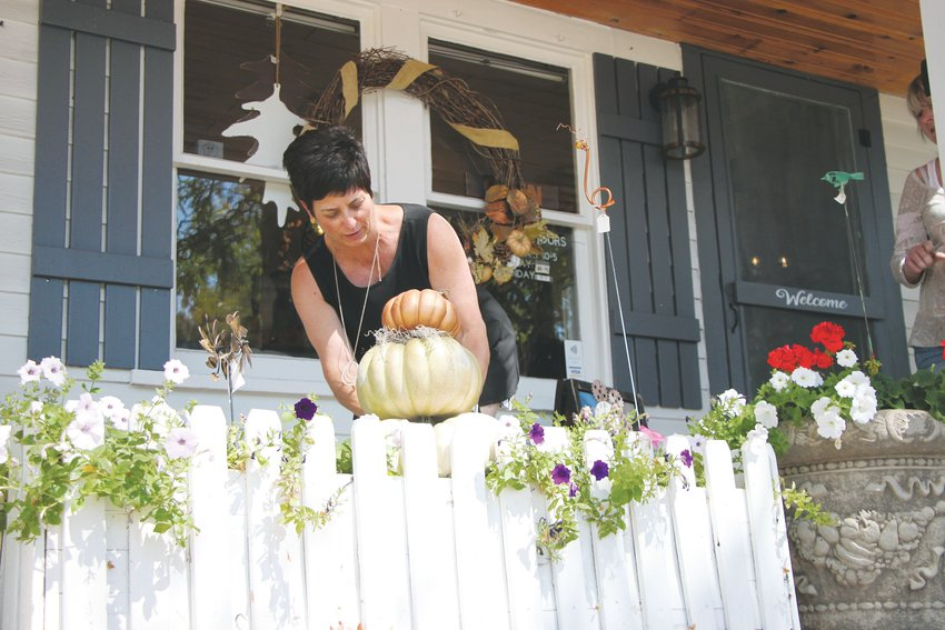 Painted Estate owner Vivien Zafferani places decorative gourds outside her shop, Painted Estate, at 2677 West Alamo Ave. Fall is a busy time at the gift and decor shop.