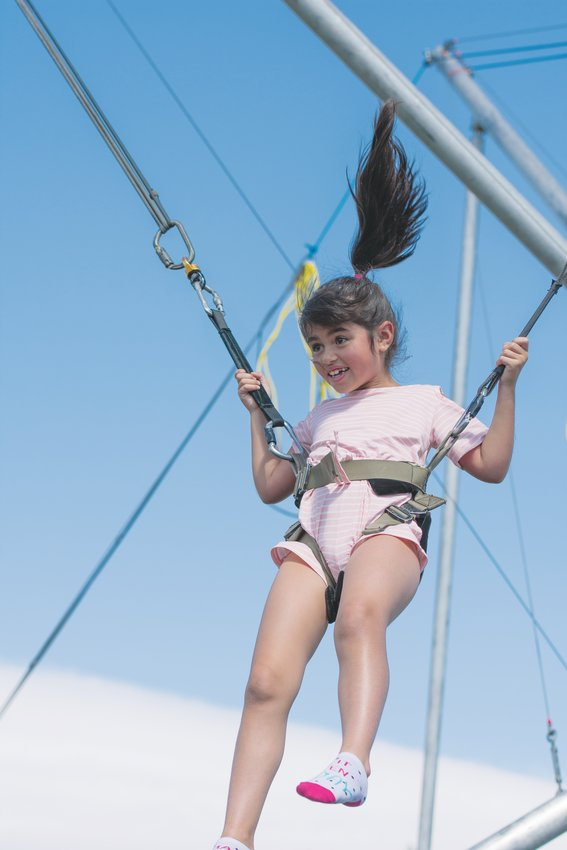 Valentina Marrero, 7, of Thornton, enjoys her time on the bunjee trampoline at the Kids Zone of this year's Thornton Harvest Fest, held Saturday, September 7, at Community Park.