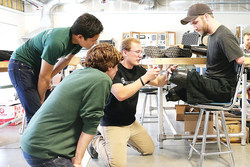 QL+ engineering students from Cal Poly work on a prosthetic device for Veteran Taylor Morris, a quad amputee and QL+ board member. QL+ recently joined the River Deep Foundation Alliance