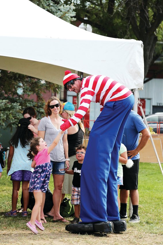 Harper Burke jumps to high-five Waldo Saturday, Sept. 7 at Ridgefest.
