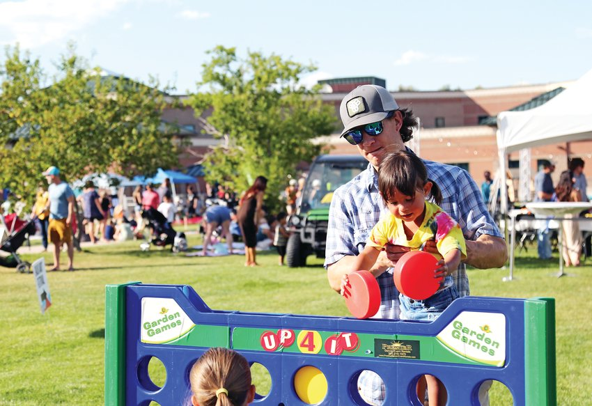 Tucker Corriveau plays with his daughter, Lina, at Ridgefest held Sept. 7 in Wheat Ridge.