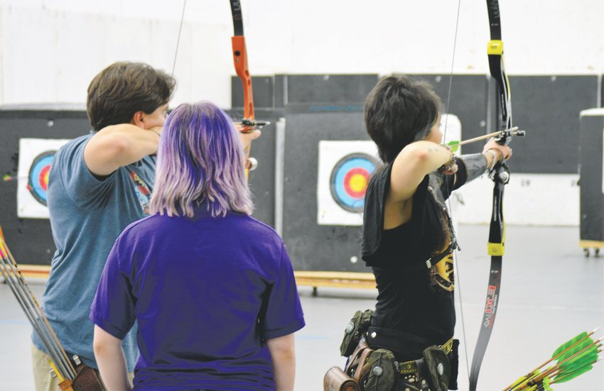 Nationally ranked barebow archers Evangeline Christel, right, and her husband Leonardo Carrasco take at aim their targets Sept. 5 at Broomfield's Empty Quiver Archery while a coach offers advice.