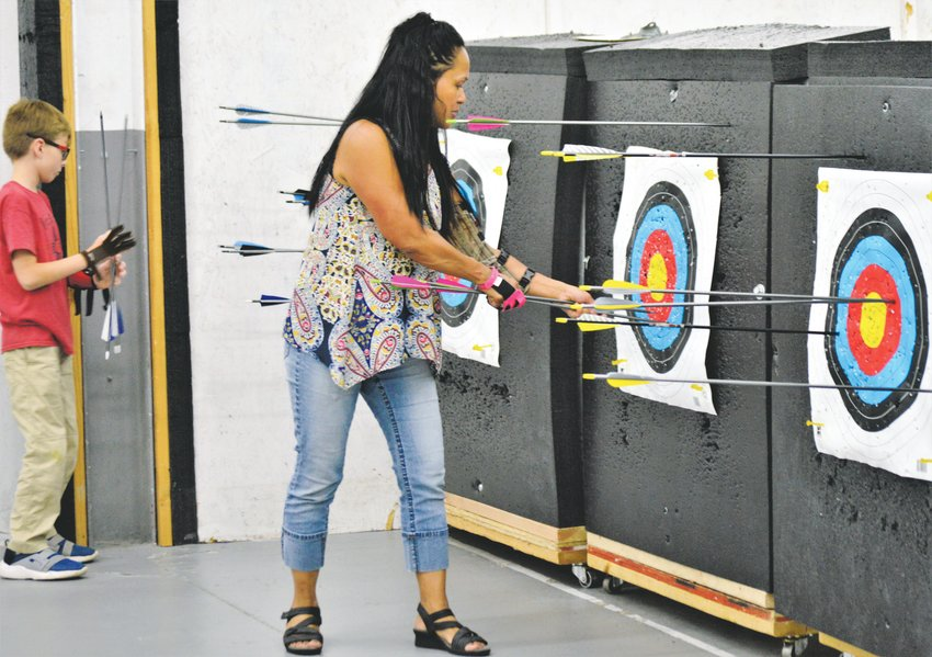 Tina Prigge of Arvada collects her arrows from the target after shooting an end Sept. 5 at Broomfield's Empty Quiver Archery.