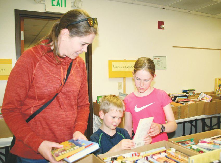 From left, Kate Borgelt, Stone Gillaspie, 5, and Mica Gillaspie, 9, pick out some books for their summer reading at the Jefferson County Library Foundation's Spring Whale of a Used Book Sale that was on May 31.