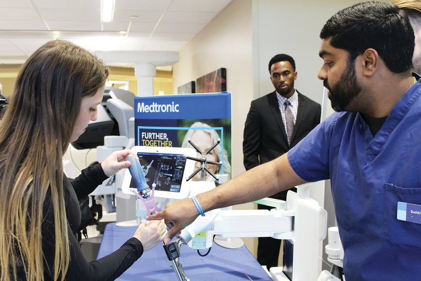 Attendees could try out the robots, as Grace Malone, left, does with assistance from Suchit Kumar, regional navigation in robotics manager for Medtronic.