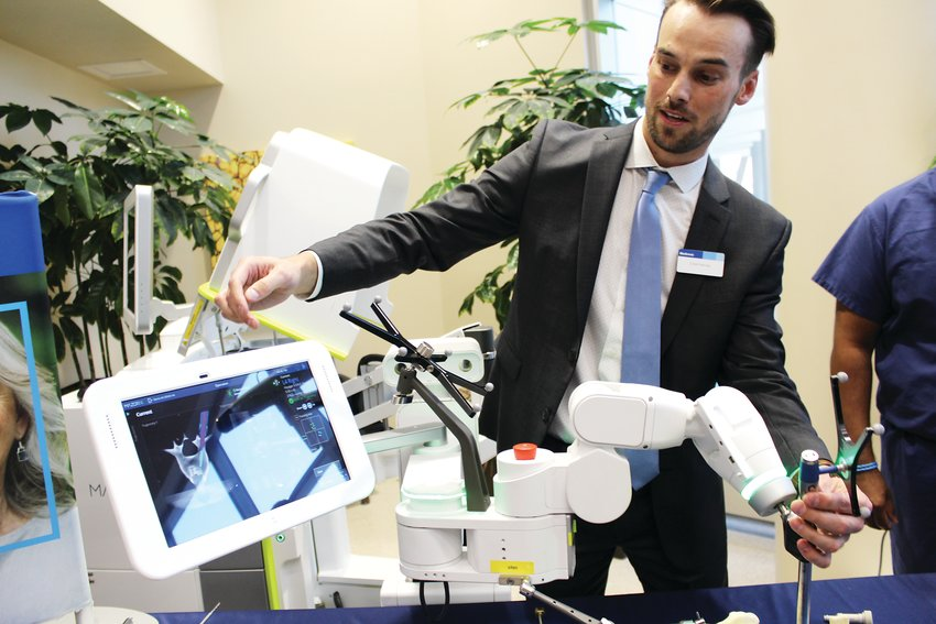 Chad Harvey, association navigation in robotics consultant for Medtronic shows off the Mazor X Stealth Edition robot. The robot is used to assist with spinal surgery.