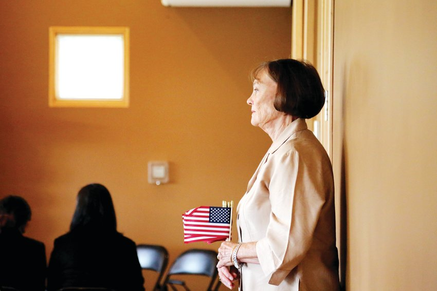 Barbara Nash, of the Peace Pipe Chapter of the Daughters of the American Revolution, waits to hand out American flags to individuals gaining U.S. citizenship at a naturalization ceremony held Sept. 6 at Four Mile Historic Park in Denver.