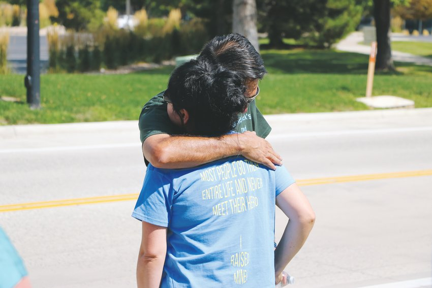 "John Castillo hugs his wife, Maria Castillo during the Run For the Fallen event Sunday, Sept. 15. The couple wears matching shirts identifying them as the teen's parents. The back of the shirts say ""Most people go their entire life and never meet their hero, I raised mine!"""