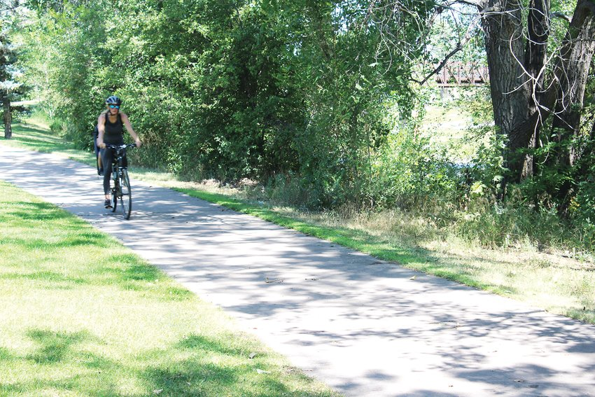A woman rides her bike recently on the South Platte River Trail in Englewood.