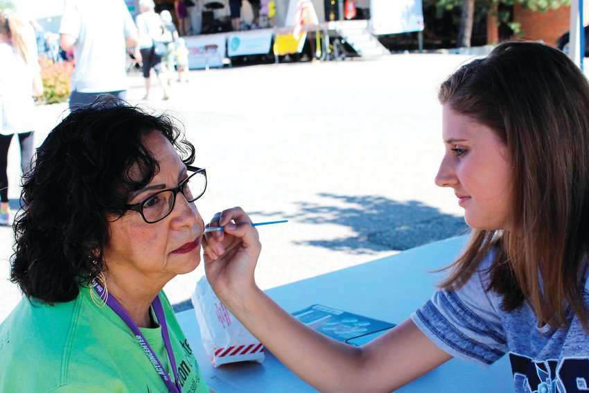 JoAnn Martinez gets her face painted by Kara Bruse. Among other activities at the Action Center's block party included games, music, a dunking tank and more.