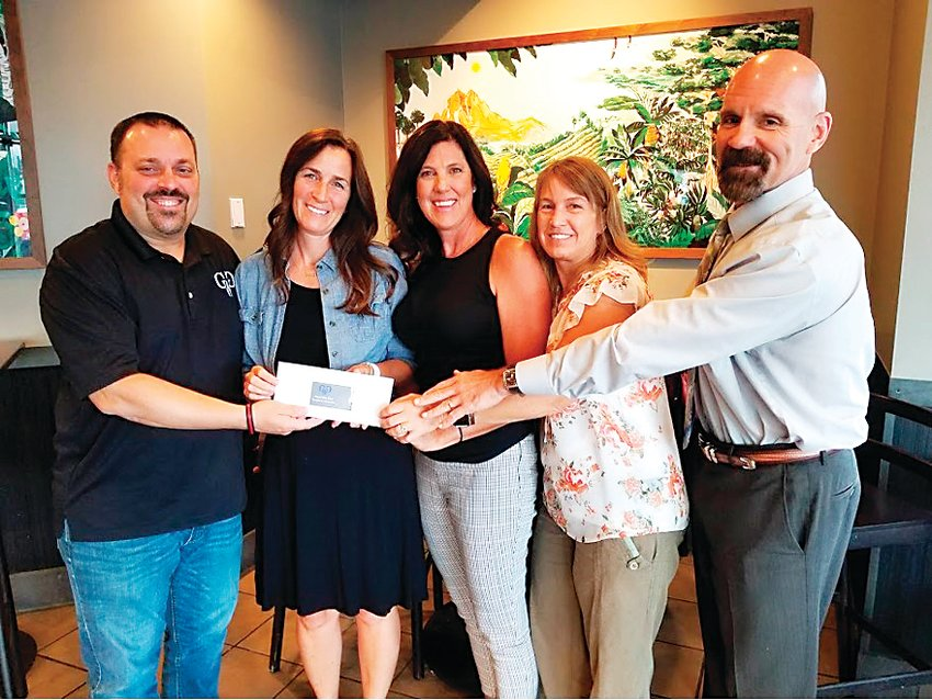 Rick Sierra, left, and Tim McCormack present the largest donation to date that Guys Who Give have raised, to RAD Advocates during their quarterly flash philanthropy meeting. From left to right: Rick Sierra, Kathleen Johnson, Amy Van Tine, Beth Cochran, Tim McCormack.