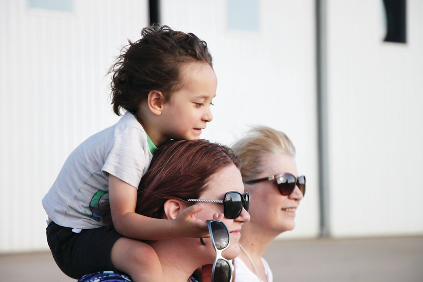 Etham Lee, 3, has his hair blown back by the propeller wash of the B-17. Lee sits on his mom Shiloh Lee's shoulders, beside grandma Gina Carpenter. Shiloh said as a high school history teacher whose grandfather served aboard a B-17, she was trying to hold back tears as she watched the plane take to the sky.