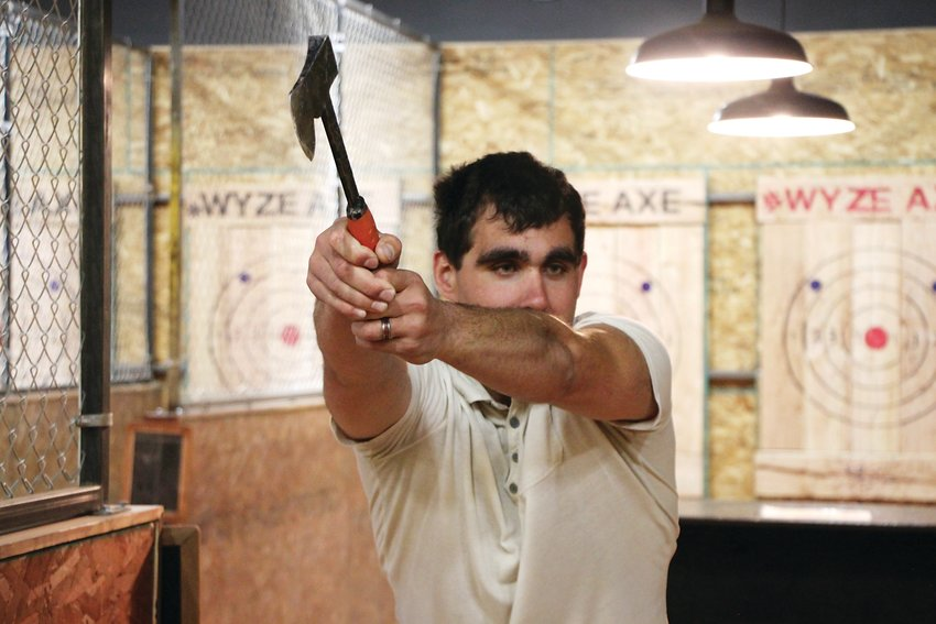 Jordan Scheremeta takes a slow-motion practice swing at Wyze Axe, an ax-throwing business in Englewood. Scheremeta nailed a few bullseyes during his first-ever round of ax throwing.