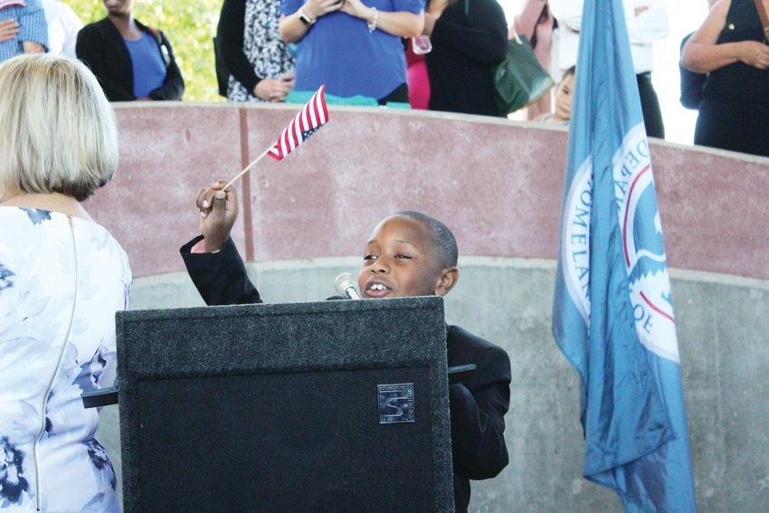 Marquis James Zikusoka, of Denver, leads a crowd of newly naturalized American citizens in the Pledge of Allegiance Sept. 25 at Centennial Center Park. His father, Prince Godfrey Zikusoka of Uganda, became a naturalized citizen during the ceremony, along with 192 others from around the Denver area.