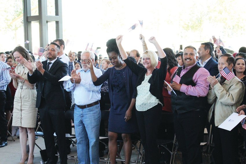 People at Centennial Center Park throw their hands in the air and cheer the moment they become naturalized citizens of the United States Sept. 25.