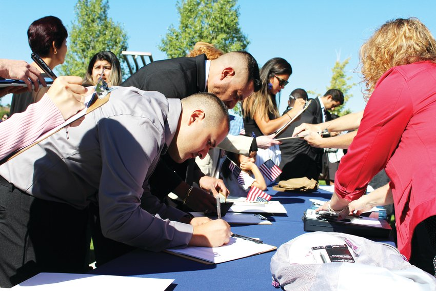 Newly naturalized citizens register to vote immediately following the naturalization ceremony at Centennial Center Park Sept. 25.